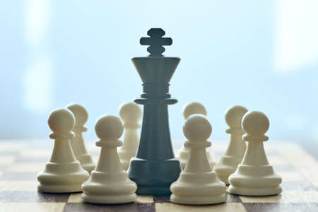 Photo pour Horizontal shot of black Queen is surrounded by white pawns. Concept of strategy and tactics. - image libre de droit