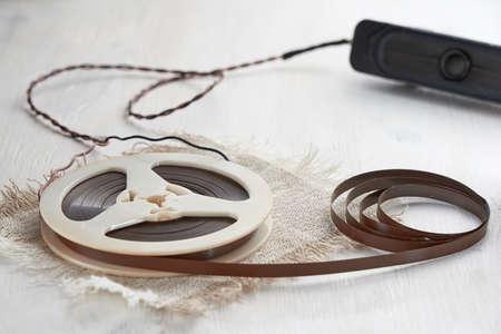 Photo pour Horizontal shot of magnetic recording tape spools on white wooden table. The concept of retro audio tape. - image libre de droit