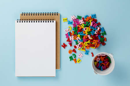 Foto de empty notebook with colored letters on a blue background top view, blank template for school concept, alphabet and back to school - Imagen libre de derechos