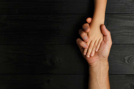 Photo pour Top view, Adult hands holding kid hands, Family Help Care Concept, small hands in fathers hand. on black wooden background - image libre de droit