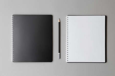 Photo for top view of a open black notebook with pencil on a gray background, school notebooks with a spiral spring, office notepad flat lay - Royalty Free Image