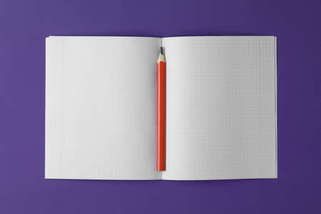 Photo for school notebook with pencil on the violet background, school notebook on the purple desk, office desk with notebook - Royalty Free Image