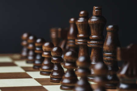 Photo pour chess pieces on a chessboard, against a dark background. Black figures stand in a row, the concept of success strategy and the right choice - image libre de droit