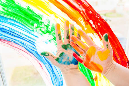 Photo pour Hands smeared with colorful paint against a rainbow on the window. Stay at home during coronavirus pandemic. Social media campaign for coronavirus prevention, chase the rainbow flashmob. - image libre de droit