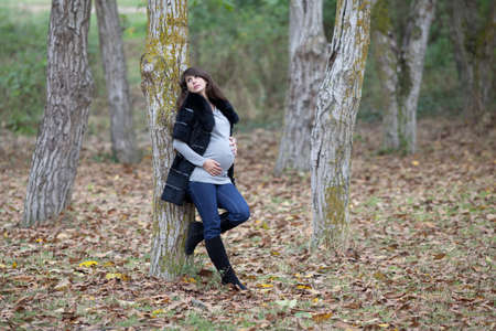 Pregnant woman in the autumn park. Expectant mother in monochrome coat in walnut grove