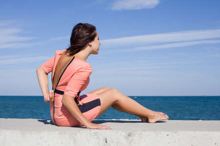 Girl at the sea  Girl unzips pink dress sitting on seashore