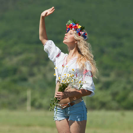 Ukrainian girl in field  Attractive blond woman in ukrainian wreath and blouse with ukrainian embroidery posing on open air