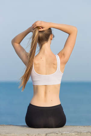 Young woman in sportswear at the sea. Slim girl sitting on concrete pier corrects own ponytail, rear view