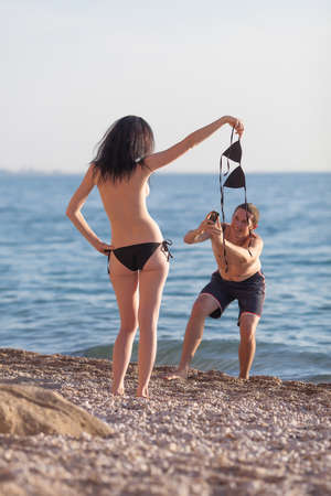 Attractive couple at the sea. Young man takes photo with phone of his topless girlfriend