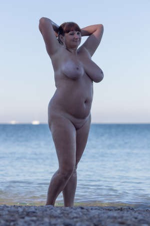 Foto de Overweight middle aged woman at the sea. Alone naked woman posing with arms raised in shadow on seashore - Imagen libre de derechos