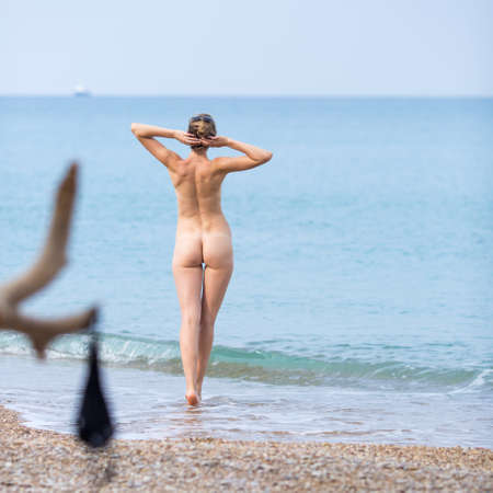 Skinny-Dipping.  Naked young woman enters in sea in cloudy day. Rear view. Square composition