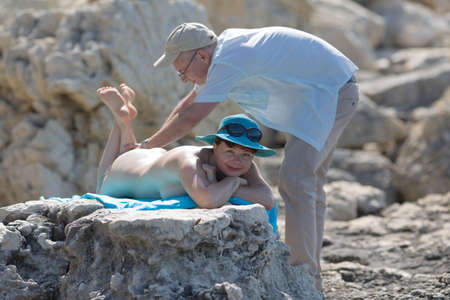 Middle aged family on wild rocky seashore. Man massaging back of his wife on rocky seashores