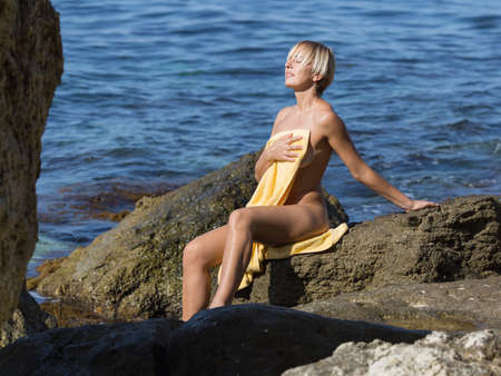 Short-haired blond woman resting in a secluded area of wild rocky seashore. Naked girl sitting on stone and drying her body with a towel on wild rocky beach