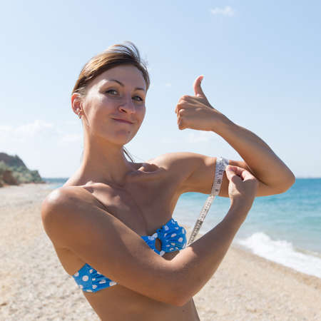 Athletic girl is measuring with a tape measure biceps and showing thumb up. Waist up portrait of young woman in blue bikini against coastline