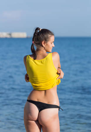 Photo for Girl undresses against sea. Young female person in black thongs takes off yellow tank top looking away - Royalty Free Image