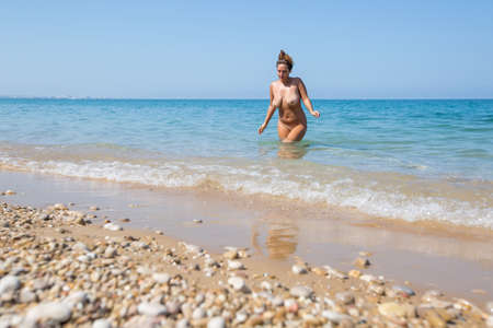 Female person resting on pebble-sandy beach. Naked young overweight woman coming out from sea