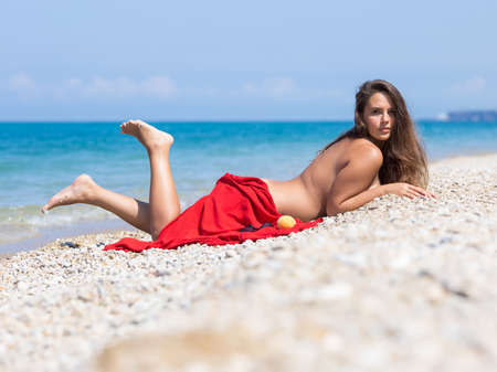 Photo pour Female person resting on pebble-sandy beach.Young overweight woman sunbathes lying on pebble - image libre de droit