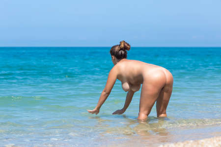 Female person resting at the sea. Naked young overweight woman entering in sea. She stands knee-deep in sea, bends and touches water
