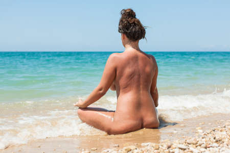 Foto de Female person resting on pebble-sandy beach. Naked young woman sits on wet sand in line of surf and looks on the sea - Imagen libre de derechos