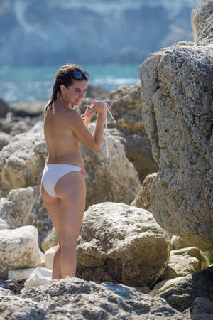 Photo pour Girl on rocky beach. Young woman takes down top of bikini and drying it among coastal stones - image libre de droit