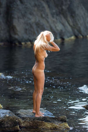 Tanned blond haired female person resting at secluded place of wild rocky seashore. Naked blonde woman standing on coastal stone. She collects her hair before bathing