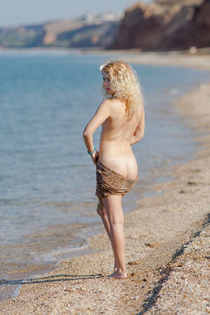 Photo for Female person posing on seashore. Blonde woman with scarf on her hips standing near waters edge - Royalty Free Image