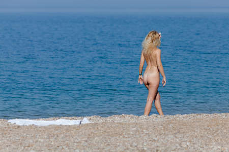 Photo for Naked girl resting on empty pebble beach. Blonde woman walking along water`s edge looking on sea - Royalty Free Image
