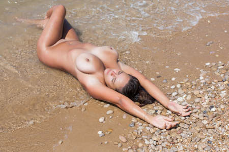 Photo pour Girl resting on pebble-sandy beach. Naked young woman lying on back on wet sand in line of surf - image libre de droit