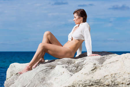 Foto de Female person resting on wild rocky seashore. Half-naked  woman in full unbuttoned, knotted shirt sunbathing on coastal rock. She sits leaning on hands and bending knees - Imagen libre de derechos