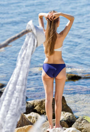 Foto de Rear view of long-haired girl in swimsuit. Young woman posing with hands behind head on seashore - Imagen libre de derechos