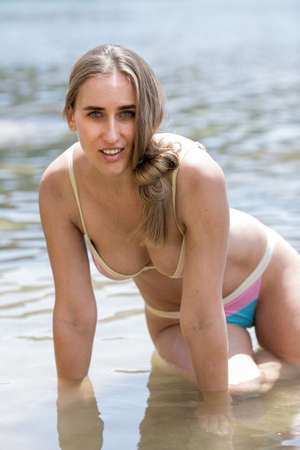 Photo pour Girl resting at the sea. Attractive female person in bikini kneeling in sea in shallow water leaning on her arms - image libre de droit