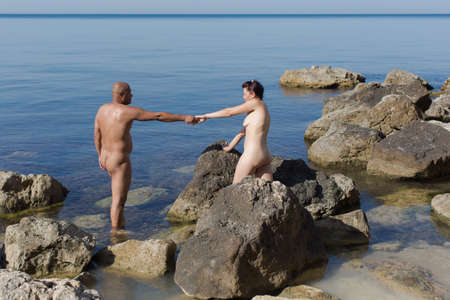 Photo pour Middle age couple at the sea in summer day. Naked husband and wife resting on wild rocky seashore - image libre de droit