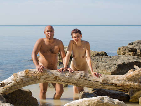 Foto de Portrait of middle age couple at the sea in summer day. Naked husband and wife posing on against sea - Imagen libre de derechos