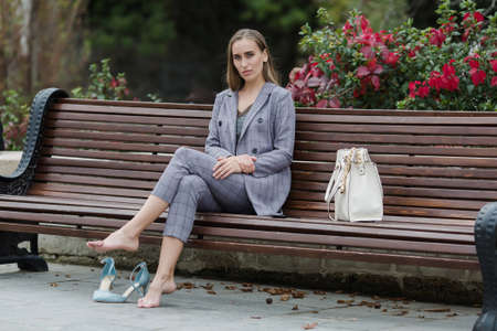 Photo pour Businesswoman in gray suit resting on bench in park. Barefoot woman sits on bench in park and looking at camera - image libre de droit