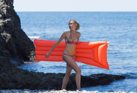 Photo pour Girl resting at the sea. Young woman in swimwear walks along coast carrying inflatable pool raft - image libre de droit