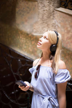 Beautiful woman visit La Pedrera with audioguide. Additional education.