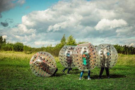 Photo pour Bumperball. Teens play bumper-ball outdoor - image libre de droit