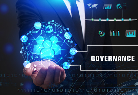 Foto de Business, Technology, Internet and network concept. Young businessman working on a virtual screen of the future and sees the inscription: Governance - Imagen libre de derechos