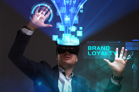 Business, Technology, Internet and network concept. Young businessman working in virtual reality glasses sees the inscription: Brand loyalty