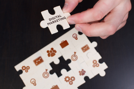 The concept of business, technology, the Internet and the network. A young businessman collects a puzzle with the proper inscription: Digital Marketing
