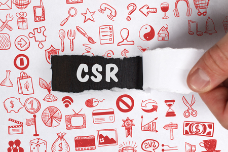The concept of business, technology, the Internet and the network. Young businessman showing inscription: CSR