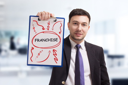 Business, technology, internet and networking concept. Young entrepreneur showing keyword: Franchise