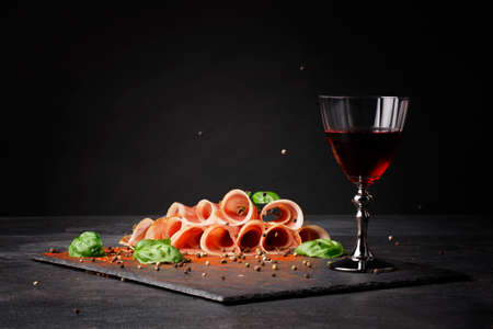 A glass of red wine and thinly sliced balyk on the saturated black background. Dry red wine, traditional Italian snacks, basil and peppercorns on the table. Copy space.の写真素材