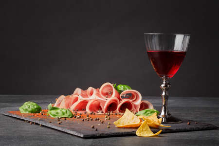 Sliced prosciutto, spicy chips and a glass of red wine on a black table backgrund. Appetixing traditional italian wine with restaurant snacks. Delicatessen, luxury, celebration concept. Copy space.の写真素材
