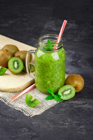 A glass of kiwi smoothie. A mason jar of green juice and a straw on a black background. Juicy kiwis on a cutting desk.