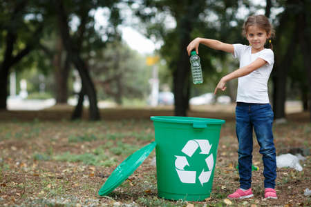 Photo for A little child putting the garbage in a green recycling bin on a blurred natural background. Ecology pollution concept. - Royalty Free Image