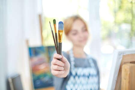 A cute girl holding a paintbrush and a box with oil paints in hands and posing on the camera in own workshop. Close-up of paintbrush. Art concept.