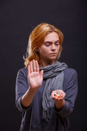 Pills in the hand of a sick girl with closed eyes on a black background.