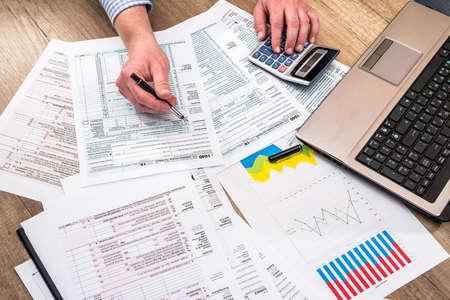 Photo pour man filling tax form with business report, chart, laptop - image libre de droit