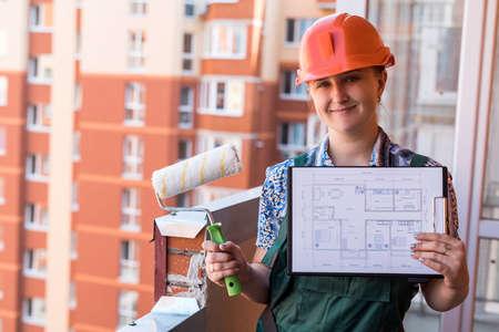Photo pour Woman builder with apartment plan posing on balcony - image libre de droit